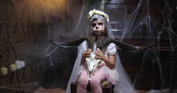 Porträt eines Mädchens im Halloween-Weihnachtsmann-Kostüm, das einen Ziegenschädel in einem alten, dunkelgotischen Interieur mit Spinnweben und geheimnisvollem Nebel und wechselnder Beleuchtung trägt. 4K Zeitlupe 50 fps