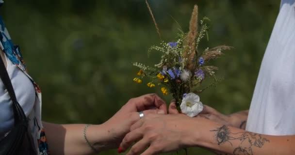 Közelíts rá a zöld hátterű, azonos nemű női párra. Két csinos, elegáns lány egymás kezét fogja, szerelmesek egy csokor virágba. 4k lassított felvétel 50 fps