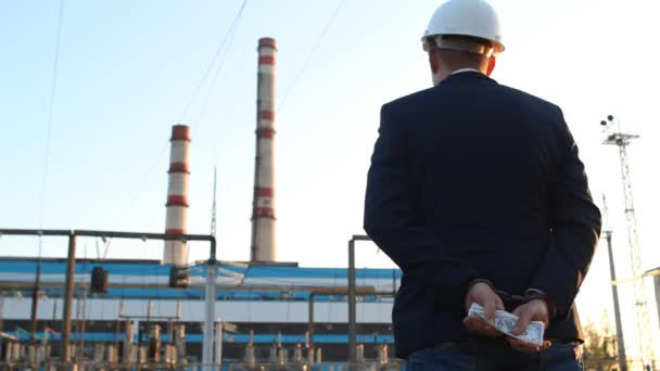 engineer chief stands with money dollars in handcuffs against the backdrop of a power plant, rear view, sunset, bribe