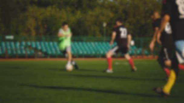 Hráč útočí, amatérský fotbal na malém stadionu v pomalém pohybu