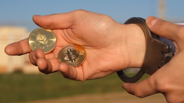 A man holds in his hand bitcoin and etherium, handcuffs, hand, close-up, handcuffs