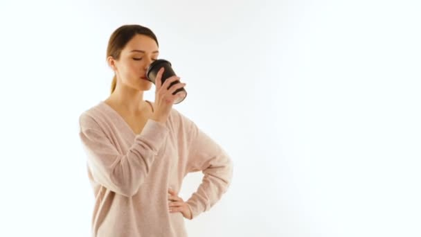 Young girl drinks from a cup of coffee, isolated