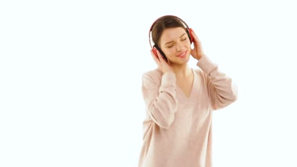 Girl listening to music with wireless headphones and dancing, isolated