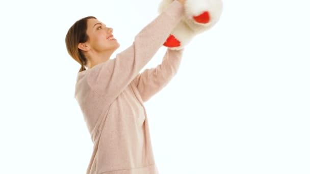 Young woman is hugging a white teddy bear and looking at the camera, isolated