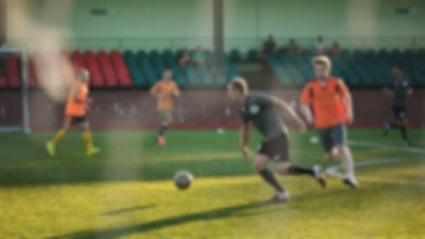 Fußballer läuft und passt den Ball, Amateurfußballspiel im kleinen Stadion in Zeitlupe, verschwommen