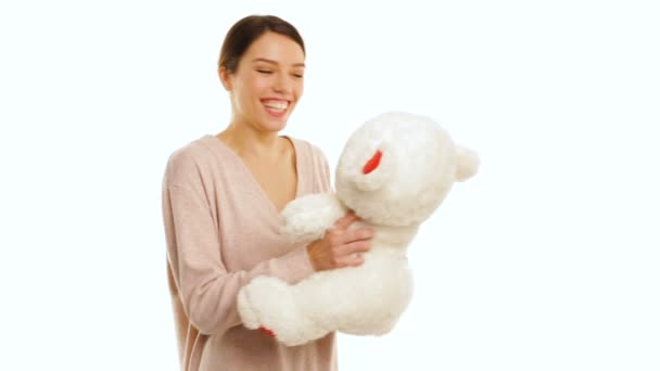 Girl is surprised by the white teddy bear with red pieces, isolated