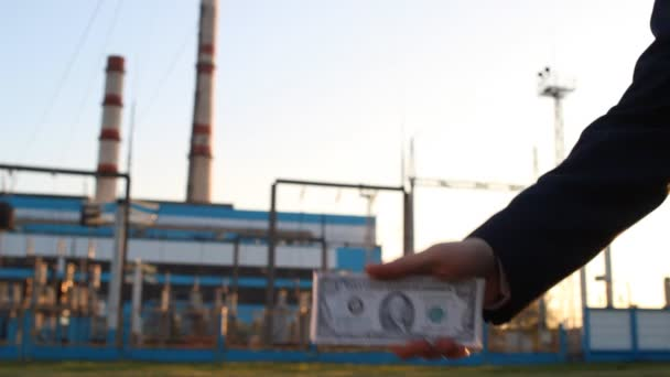 A hand with money dollars against a power plant background is handcuffed, close-up, sunset, bribe, arrest