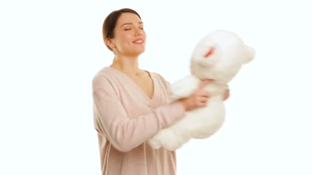 Young woman is hugging a white teddy bear with red pieces, isolated