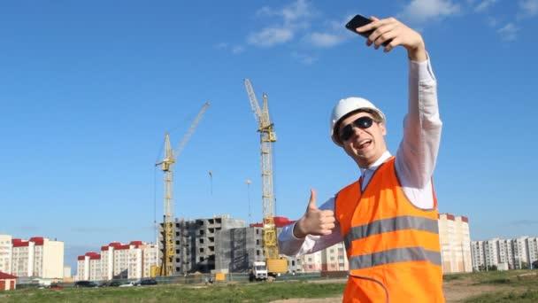 Vrchní inspektor dělá selfie na pozadí stavby domu