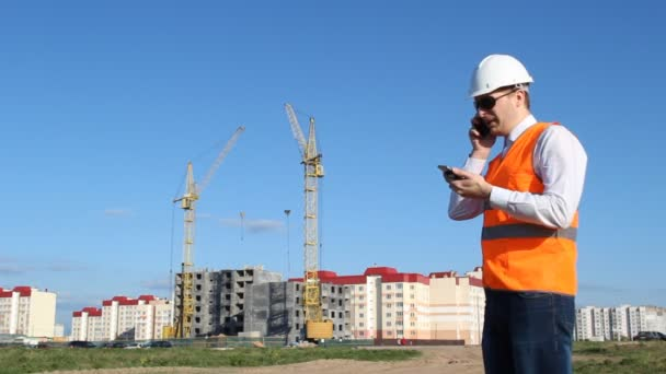 Hlavní inspektor hovoří o dvou telefonů na pozadí stavby domu