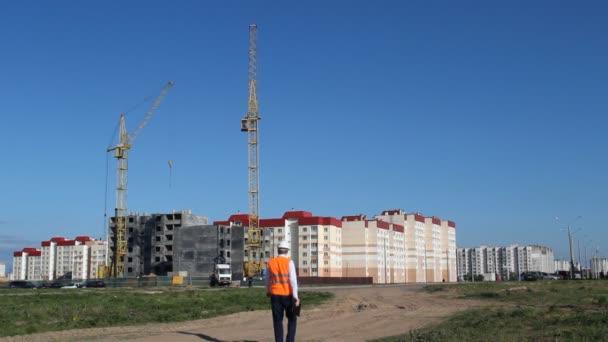 náčelník jde a zkoumá stavbu bytového domu