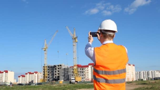 Inspektor v bílou helmu a vestu alarm je fotografování výstavbu bytového domu