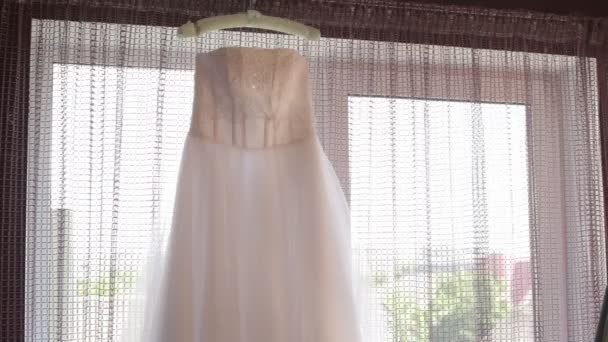 Beautiful wedding dress hanging in the room