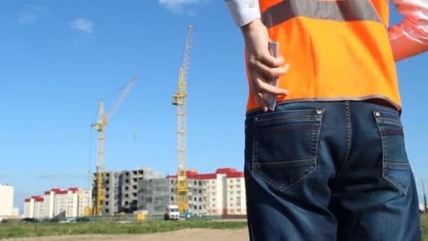 Vedoucí inspektor klade peníze v zadní kapse kalhot, v pozadí výstavby