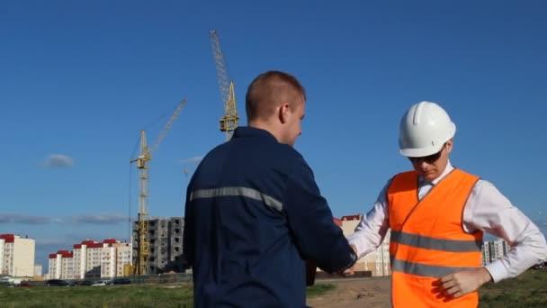 Zaměstnanec přináší dokumenty k podpisu na vrchní inspektor, pozadí výstavby bytového domu