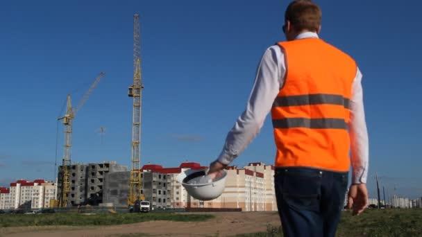 Inspektor v signální vesta kontroluje výstavbu objektu bytového domu