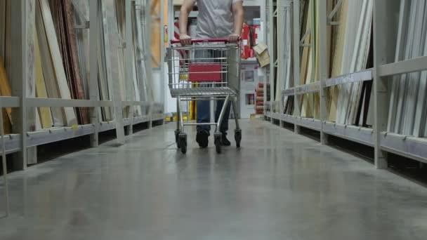 mužské kupující s nákupním košíku chodí v úložišti
