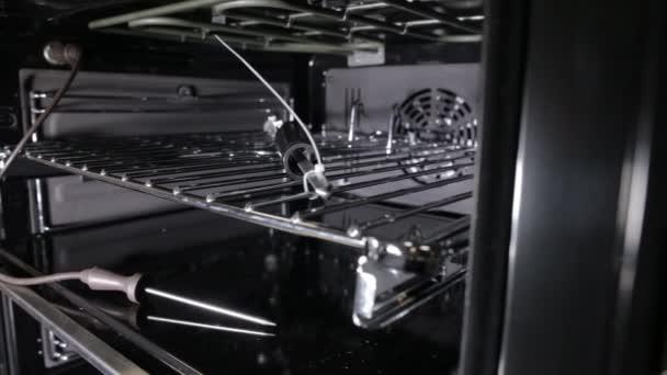 Černý stylový a moderní plynový sporák s konvekcí, detail, pohled dovnitř, gril