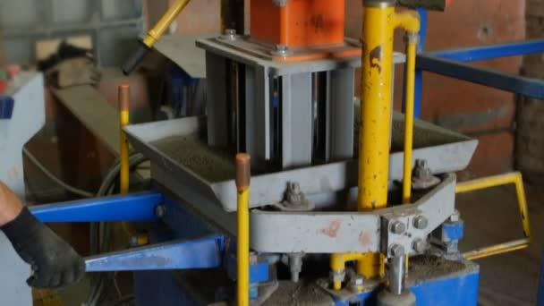 Výrobní proces betonové dlaždice bloků v podobě cihel na povrchu krytu vozovky. Vibrocompression a komprimaci polosuchého betonu tím lis