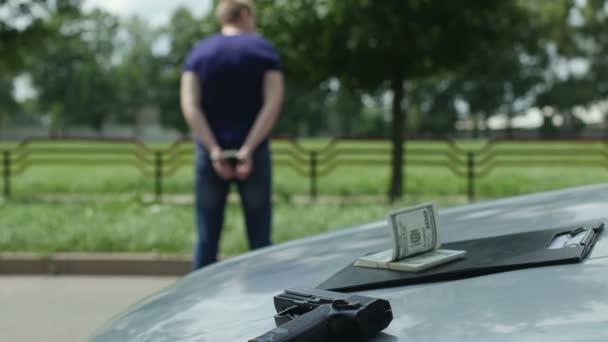 zadržené zločinec v poutech stojí poblíž ukradené auto