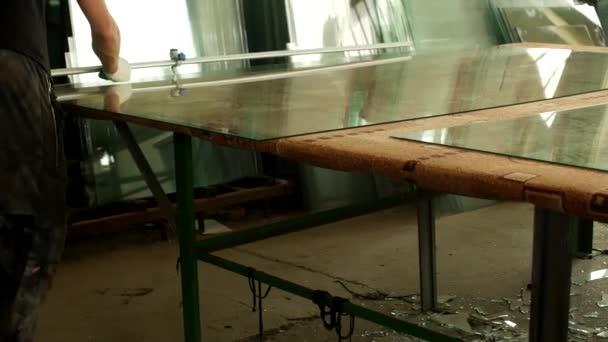 Dílna na výrobu izolačního skla, pracovník dělené sklo s brusičem skla pro další montáž útvaru pro izolační skla, broušení skla