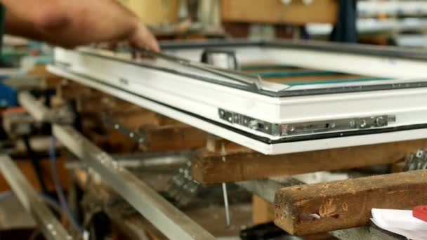 Výroba a výroba plastových oken, muže pracující na pvc profilu okna, zavěsí snap, montáž oken, zařízení