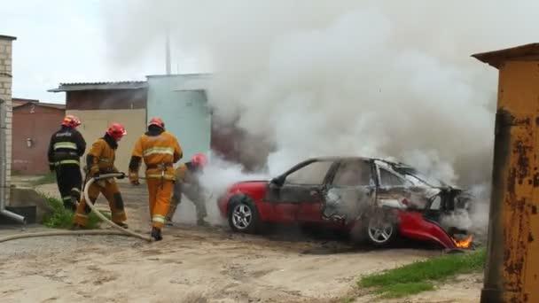 Bobruisk, Bělorusko - 25 července 2018: hasiči nebo hasičům uhasit hořící osobní automobil po aktu terorismu