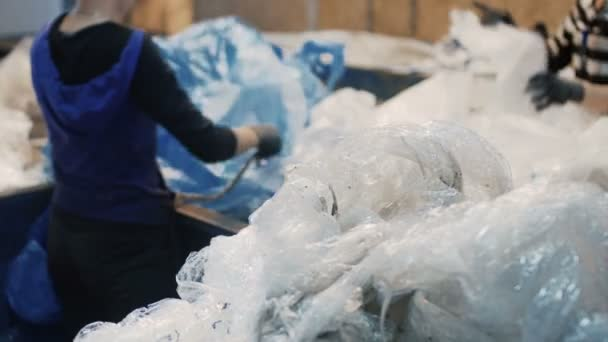 Women sorting by hands garbage in the form of polyethylene for further waste recycling