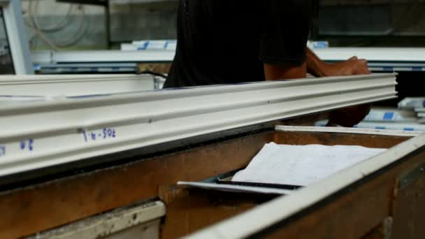 Výroba a výroba plastových oken, mužský pracovník nainstaluje pryžová těsnění v rámu Pvc, sestavuje Pvc okna, výrobní