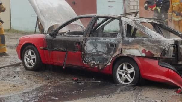 Hasiči nebo hasiči nalijte vodu na spálené auto