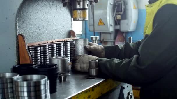 Pracovník sestaví lisování ložiska do kovového klipu na stroji, sestavuje dokončené jednotky, close-up, tisk, pracovní