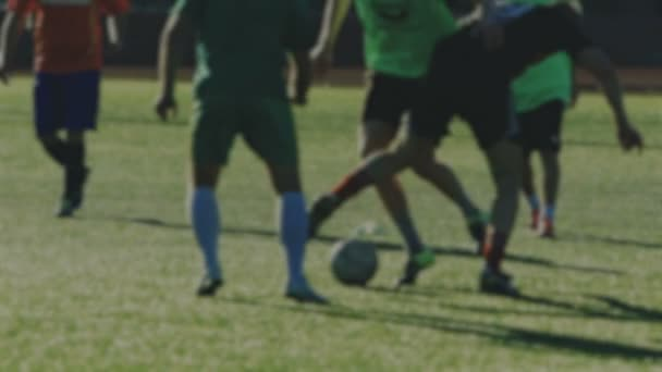 Soccer players run and shoot a ball, blurred for background