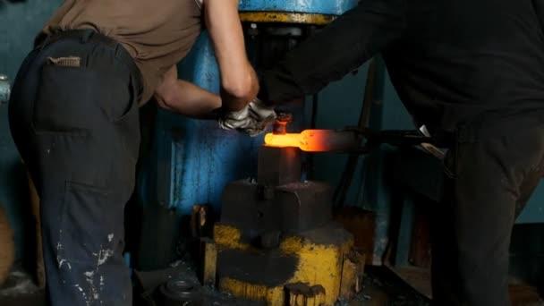 Dva kováři v kovárně se kovové části pro stroje stavební stroj, horký kov a kovárna, jiskra, slow-mo