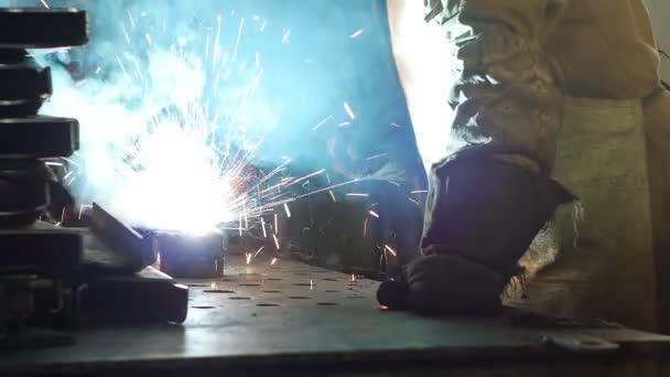 Svářeč svary kovových dílů, svařování kovů, průmyslu a průmyslu, detail, pomalý pohyb