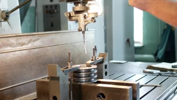 Der Fachmann prüft das Messwerkzeug in der Größe einer Metallrolle und setzt einen Bohrer in eine Bohrmaschine ein.