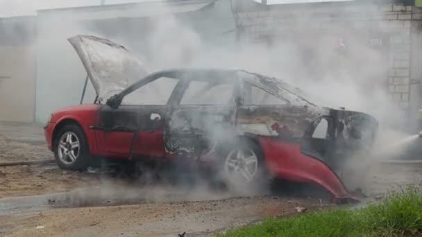 Bobruisk, Bělorusko - 25 července 2018: hasiči nebo hasiči uhasit spálené auto po aktu terorismu