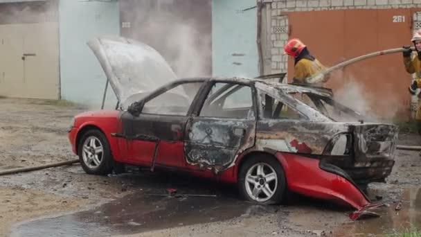 Bobruisk, Bělorusko - 25 července 2018: hasiči nebo hasičům uhasit hořící automobil po samovznícení