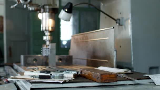 eine private Werkstatt für die Bearbeitung von Metallteilen, im Hintergrund bohrt eine Bohrmaschine ein Loch in die Riemenscheibe, auf dem Tisch liegen Messwerkzeuge, Produktion, Werkstatt