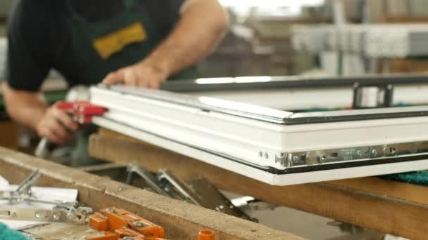 Výroba a výroba plastových oken, mužské pracovník sestavuje profil pvc okna, spojuje výklopné části, pvc okna