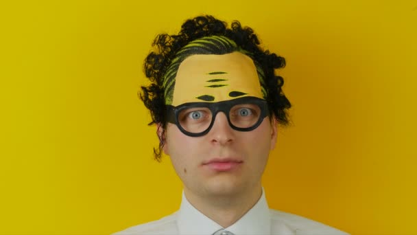 Portrét šokován a překvapen kudrnaté muž, zábavný a vesele emoce, na pozadí žluté zdi