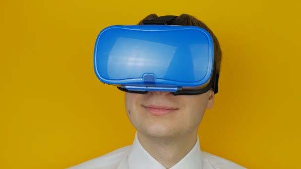 Ein glücklicher Mann mit blauem Head-Mounted-Display schaut sich um, Virtual Reality, hmd 360