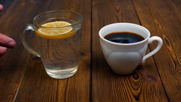 člověk vybírá vodu s citronem místo šálek kávy pro zdravý životní styl