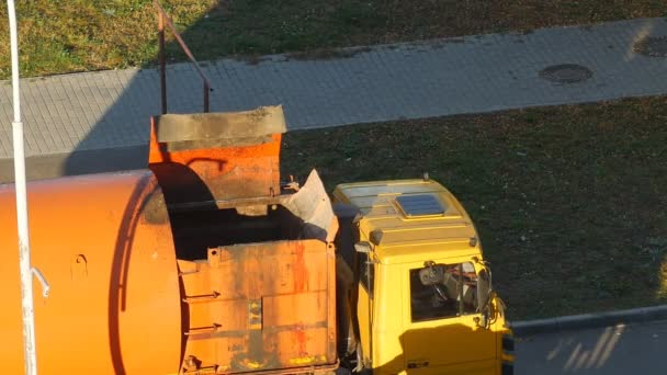A garbage truck cleans garbage cans in the courtyard of a residential area from garbage and takes it to landfill, close-up, garbage removal, hydraulics