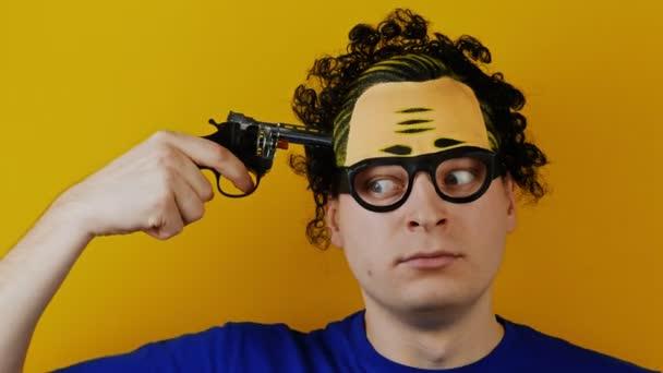 komický člověk s hračkou pistole pistole střílí sebe v hlavě pro zábavu