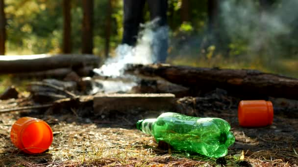 In the foreground in a forest glade there are plastic bottles of garbage, fires are smoking, people walk in the background, outdoor recreation, pollution by garbage