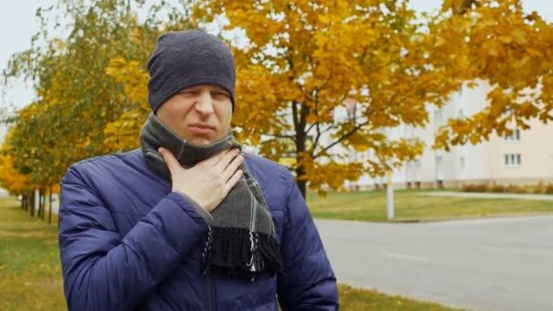 nemocní nebo nemocný člověk bere prášek nebo tablety proti bolesti v krku v důsledku chřipky virus chřipky ve městě nebo přírodě na podzim a na podzim