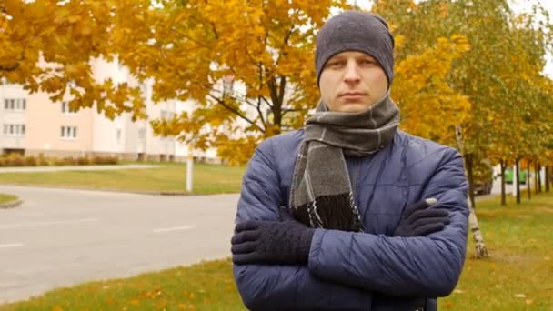 portrait of man wearing scarf and hat in the fall or autumn outside, in city