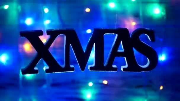 Vánoční nápis Xmas volně visí ve vzduchu, na dřevěné pozadí, nový rok světla, novoroční svátky, pozadí 2019, Vánoce, nový rok