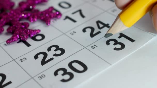 Az asztalon van, a December naptár a újév kéz felhívja egy ceruza azon a napon, December 31-én, közelkép, az új évben 2019, hagyományos