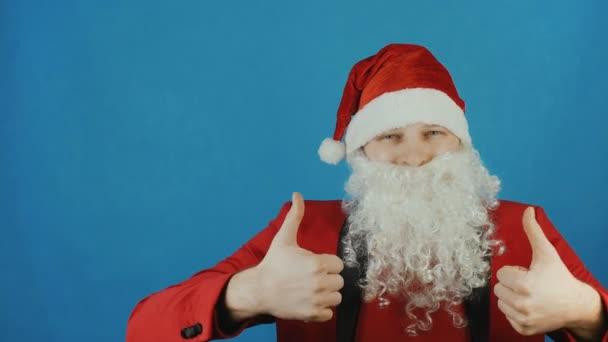 Vánoce a nový rok 2019, člověk jako Santa Claus ukazuje palec nahoru jako na modrém pozadí